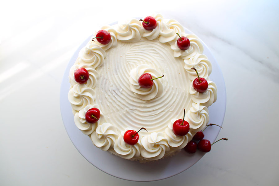This decadent white Chocolate cake is irresistibly delicious. Filled with white chocolate chips or Chunks and topped with silky white buttercream, it makes an elegant and beautiful bake for any occasion.