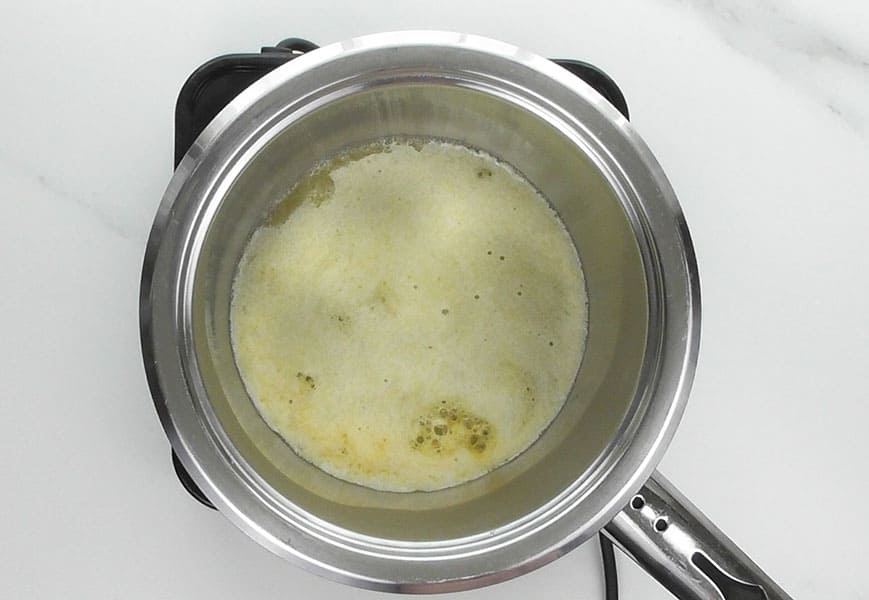 As the butter melts it starts to splatter and foam begins to rise to the surface. The splattering means that the water in the butter is evaporating. Continue to simmer the butter until the splattering subsides, about 6-7 minutes.